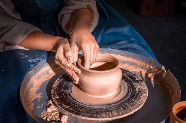 Mulher ceramista sentada em um banco com uma roda de oleiro e fazendo pote de barro