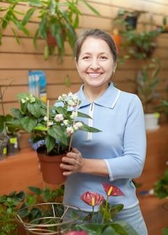 Mulher cercada por flores diferentes em loja de flores