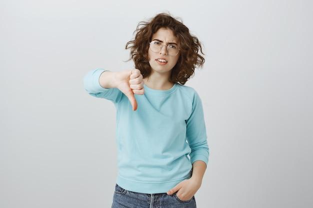 Mulher cética e decepcionada mostrando polegar para baixo, resultado péssimo