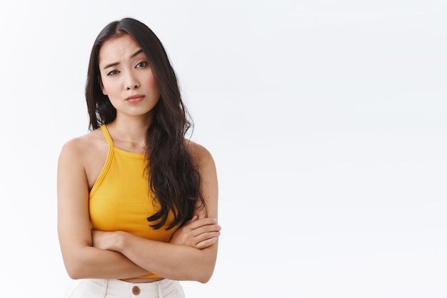 Mulher cética e pouco impressionada do leste asiático em blusa amarela, cruza as mãos no peito, postura defensiva e desinteressada, levanta uma sobrancelha e olha para o julgamento, sendo impassível e duvidosa
