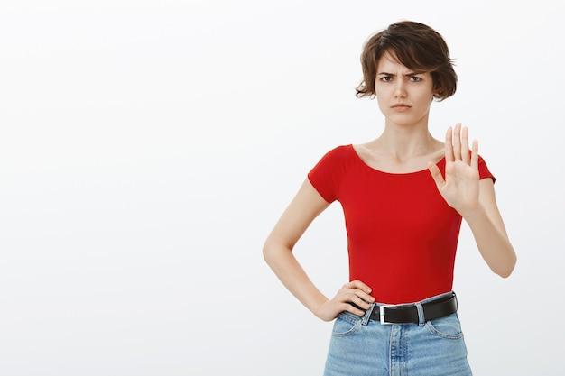 Mulher cética e relutante levantando as mãos em rejeição, recusando a oferta, dizendo para parar