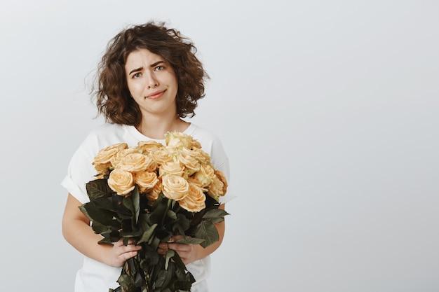 Mulher cética e sorridente segurando um buquê de rosas sem expressão impressionada
