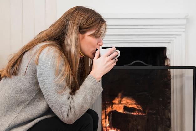 Mulher, chá bebendo, perto, lareira