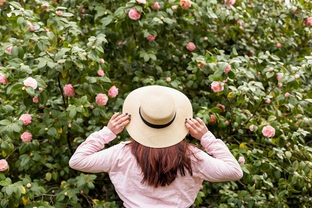 Mulher chapéu, perto, flores cor-de-rosa, crescendo, ligado, verde, ramos