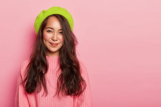 Mulher charmosa com longos cabelos escuros, usa boina verde e suéter rosado