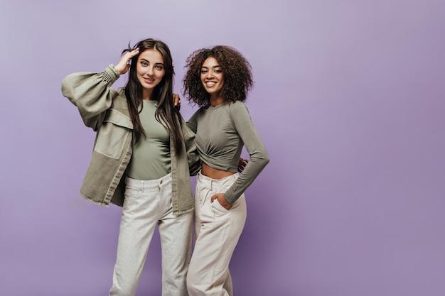 Mulher charmosa de cabelos cacheados em top oliva e calça branca, sorrindo e se abraçando com uma garota elegante em um casaco na parede lilás