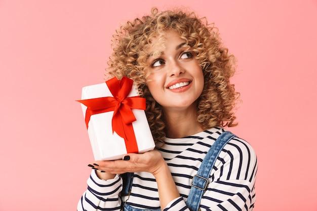 Mulher charmosa e cacheada de 20 anos segurando uma caixa de presente em pé