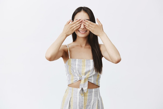 Mulher charmosa e elegante de top e shorts fechando os olhos com as palmas das mãos e sorrindo amplamente, brincando de esconde-esconde ou esperando surpresa com empolgação