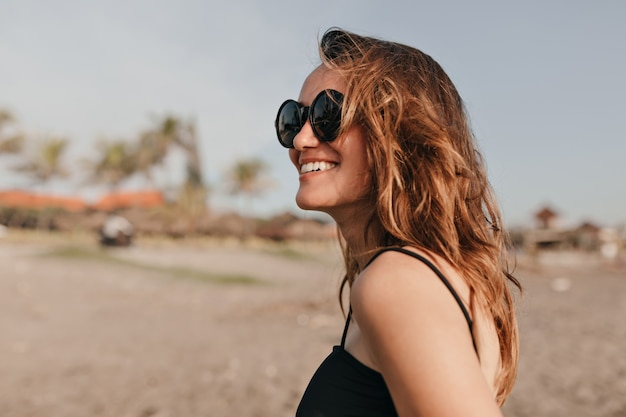 Mulher charmosa e feliz e sorridente com cabelo escuro ondulado caminhando sob o sol na praia e curtindo as férias no oceano