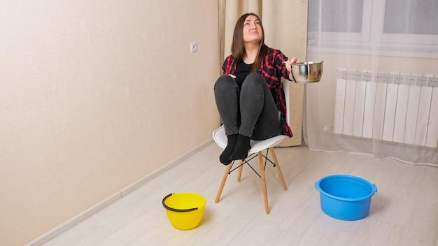 Mulher chateada coleta água descendo do teto da sala