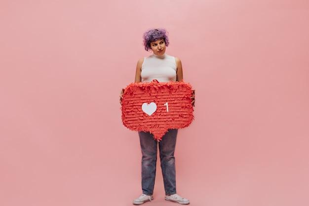 Mulher chateada com blusa branca, calça jeans e tênis leves desvia o olhar e segura uma enorme placa vermelha como em rosa isolada.