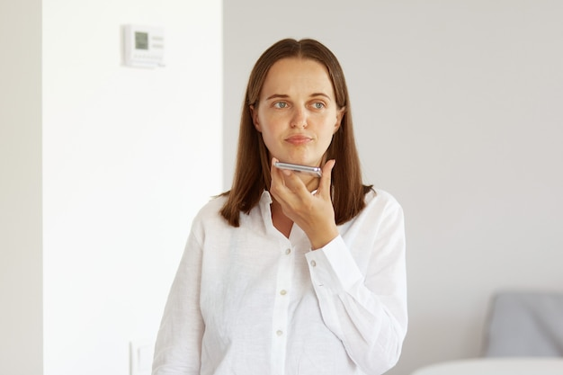 Mulher chateada com cabelo escuro, vestindo uma camisa branca estilo casual, olhando para longe, posando em uma sala clara em casa, gravando um comando de voz ou mensagem, em pé com beicinho e expressão facial insatisfeita