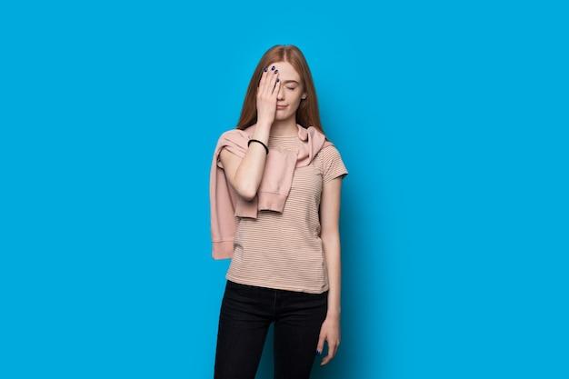 Mulher chateada com cabelo ruivo e sardas gesticulando com a palma da mão no rosto sobre um fundo azul