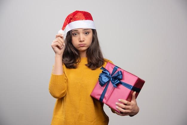 Mulher chateada com chapéu de papai noel vermelho com presente de natal.