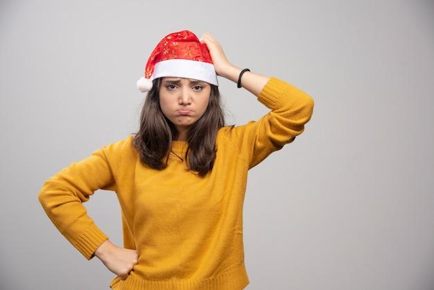 Mulher chateada com chapéu de papai noel vermelho posando sobre uma parede branca.