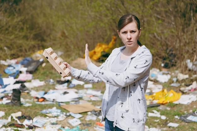 Mulher chateada com roupas casuais, limpando segurando lixo e mostrando gesto de pare com a palma da mão em um parque cheio de lixo