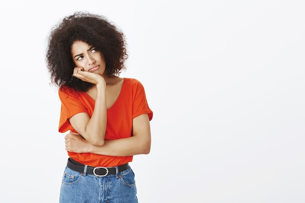 Mulher chateada com um penteado afro posando no estúdio
