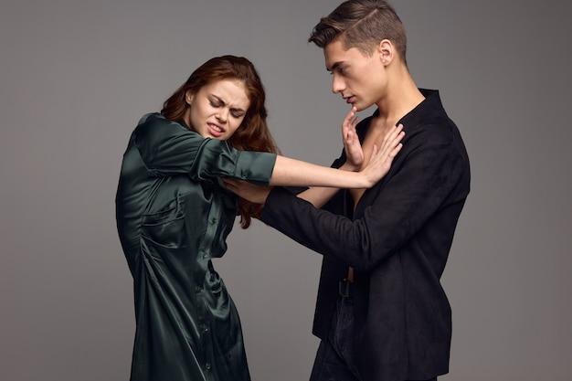 Mulher chateada com um vestido empurra o homem para o lado contra um fundo cinza. foto de alta qualidade