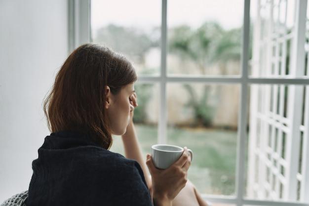 Mulher chateada com uma xícara de café pela manhã
