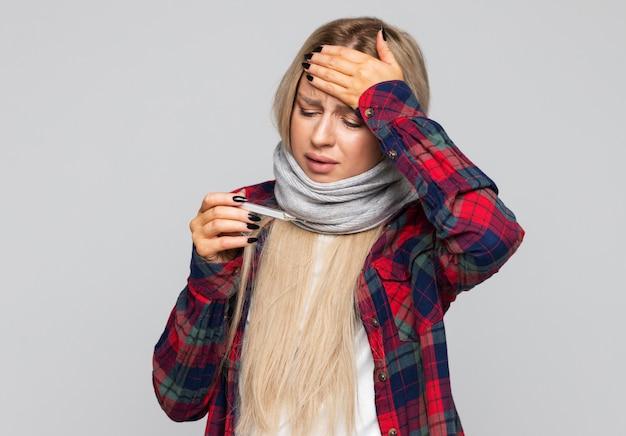 Mulher chateada, de camisa quadriculada, enrolada em lenço, com sintoma de gripe