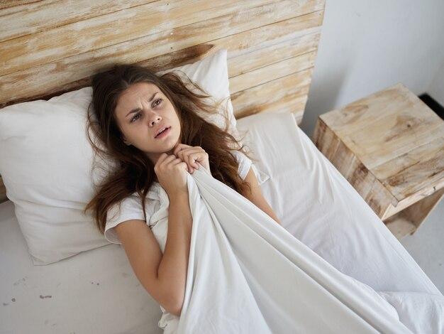 Mulher chateada deitada na cama sob as cobertas e olhando para cima