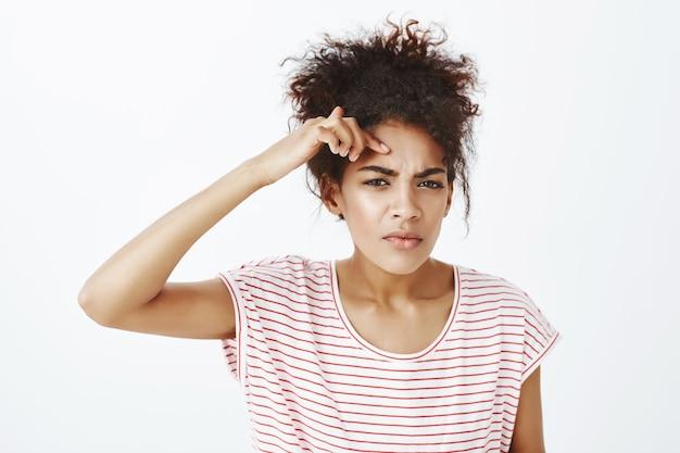 Mulher chateada descontente com penteado afro posando no estúdio
