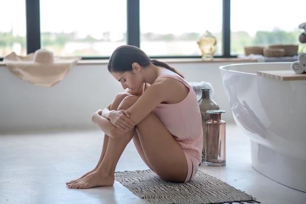 Mulher chateada e estressada sentada no chão do banheiro
