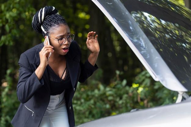 Mulher chateada falando ao telefone sobre o motor do carro dela não funcionar