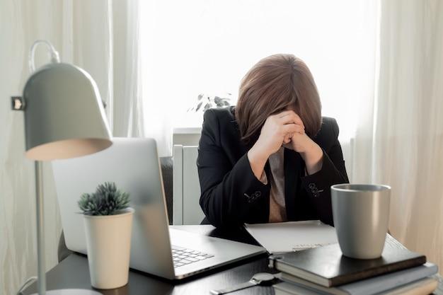 Mulher chateada fechou sua cara de mãos perto de seu local de trabalho com laptop e currículo o aplicativo.