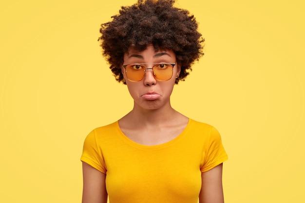 Mulher chateada franze o lábio inferior e se sente insultada, tem pele morena, parece desagradada, usa camiseta amarela casual