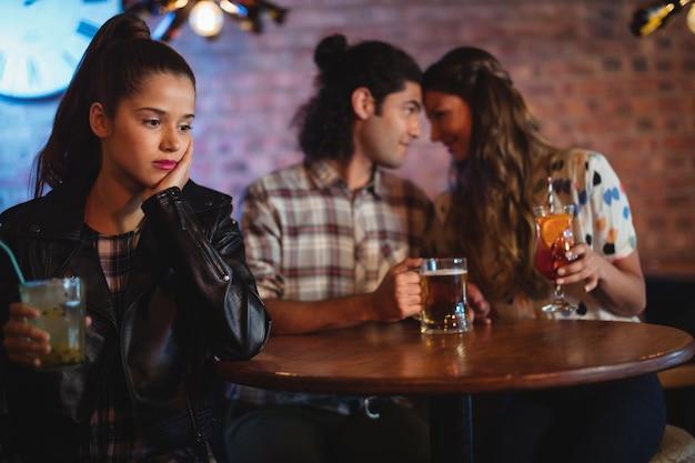 Mulher chateada ignorando casal afetuoso