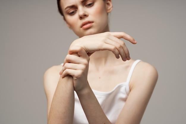 Mulher chateada move a mão para o lado do osso quebrado do pulso