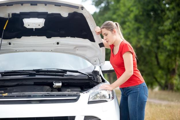 Mulher chateada olhando sob o capô de um carro superaquecido no campo