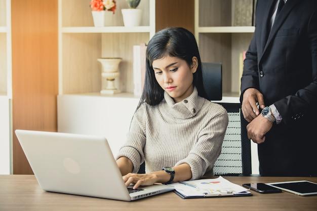 Mulher chateada sendo repreendido pelo chefe para trabalhar no escritório