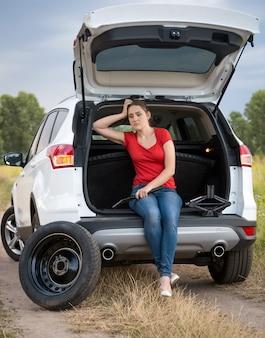Mulher chateada sentada na mala do carro e esperando ajuda para trocar o pneu