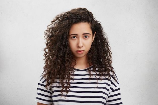 Mulher chateada tem cabelo crespo, expressão carrancuda ou sombria, e fica descontente