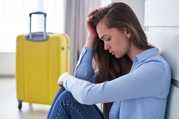 Mulher chateada viajante com sua bagagem no aeroporto