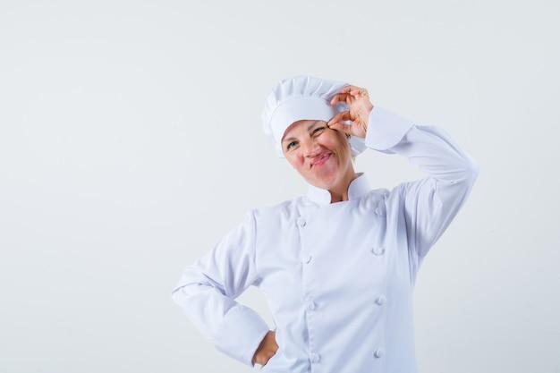 Mulher chef beliscando a pálpebra em uniforme branco e parecendo estranha