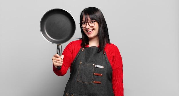 Mulher chef bonita de tamanho grande cozinhando com uma panela