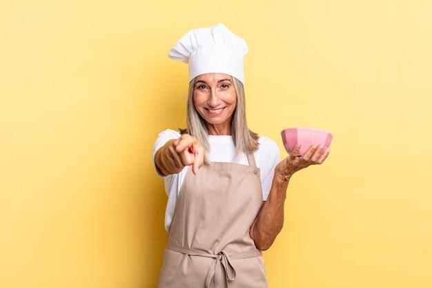 Mulher chef de meia-idade apontando para a câmera com um sorriso satisfeito, confiante e amigável, escolhendo você e segurando uma panela vazia