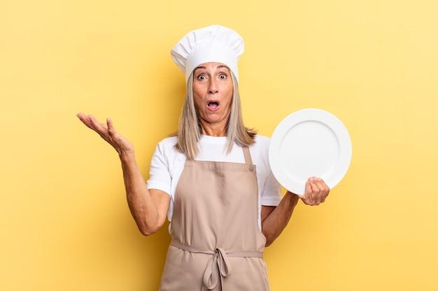 Mulher chef de meia-idade boquiaberta e pasma, chocada e atônita com uma surpresa inacreditável e segurando um prato
