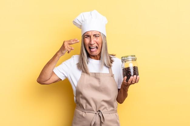 Mulher chef de meia-idade parecendo infeliz e estressada, gesto suicida fazendo sinal de arma com a mão, apontando para a cabeça segurando grãos de café