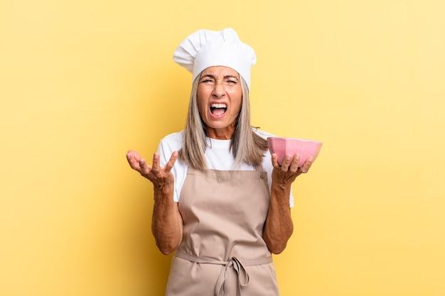 Mulher chef de meia-idade parecendo zangada, irritada e frustrada, gritando wtf ou o que há de errado com você e segurando uma panela vazia
