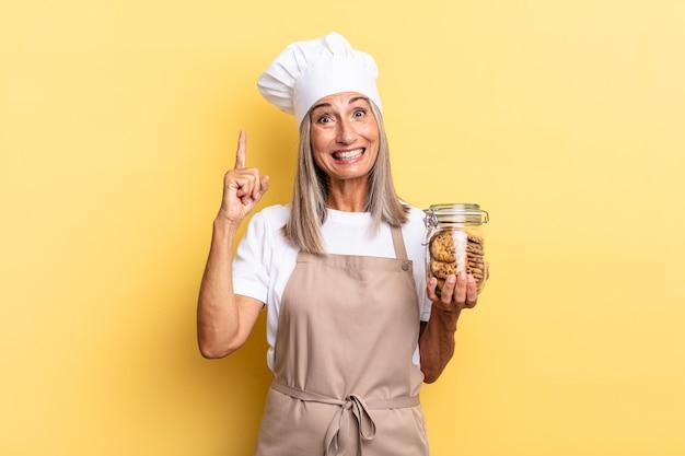 Mulher chef de meia-idade se sentindo como um gênio feliz e animado depois de realizar uma ideia, levantando o dedo alegremente, eureka! com biscoitos