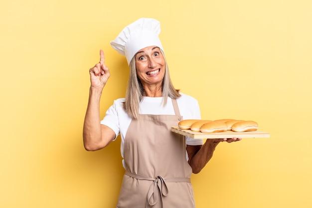 Mulher chef de meia-idade se sentindo como um gênio feliz e animado depois de realizar uma ideia, levantando o dedo alegremente, eureka! e segurando uma bandeja de pão