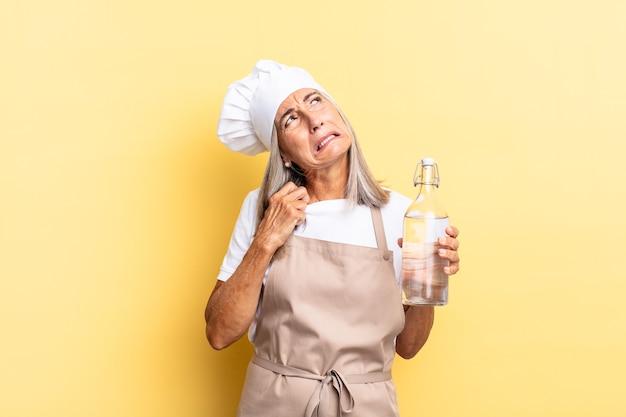 Mulher chef de meia-idade se sentindo estressada, ansiosa, cansada e frustrada, puxando o pescoço da camisa, parecendo frustrada com o problema com uma garrafa de água