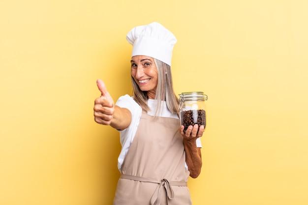 Mulher chef de meia-idade se sentindo orgulhosa, despreocupada, confiante e feliz, sorrindo positivamente com o polegar para cima segurando grãos de café