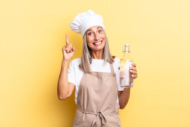 Mulher chef de meia-idade se sentindo um gênio feliz e animado depois de realizar uma ideia, levantando o dedo alegremente, eureka! com uma garrafa de água