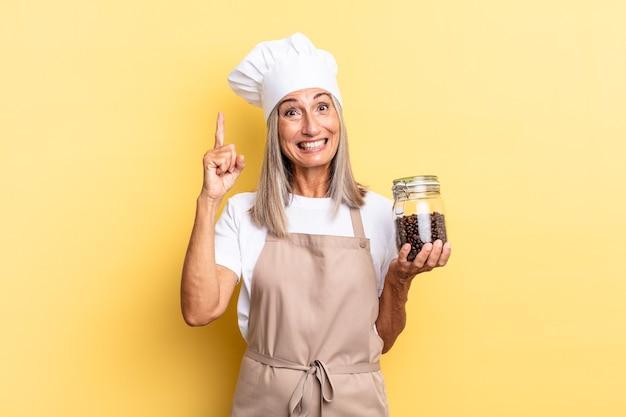 Mulher chef de meia-idade se sentindo um gênio feliz e animado depois de realizar uma ideia, levantando o dedo alegremente, eureka! segurando grãos de café