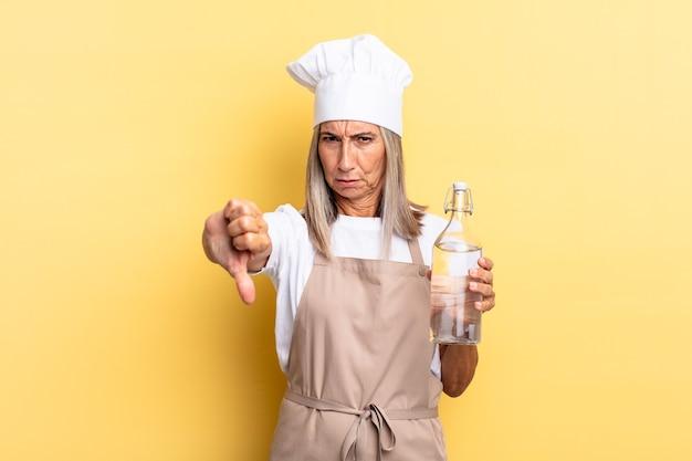 Mulher chef de meia-idade se sentindo zangada, irritada, irritada, decepcionada ou descontente, mostrando o polegar para baixo com um olhar sério com uma garrafa de água